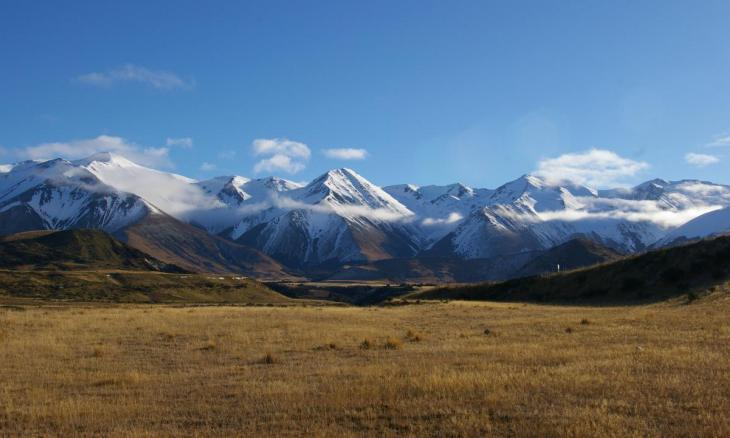 Snowy mountains shrouded in cloud with a blue sky background.